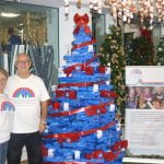 Mary and her husband from Francis House stood with the Midshire donation to the Festival of Christmas Trees