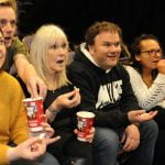 Group shot of NK theatre staff watching a play with Midshire donated popcorn
