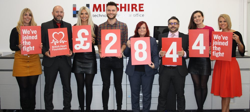 Midshire staff holding the final amount raised at a charity cycle for the British heart foundation