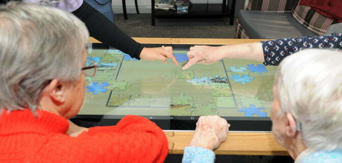 Touchscreen tables being used by the elderly